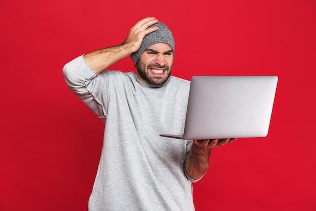 Porträt des verwirrten kerls 30s in der freizeitkleidung, die kopf ergreift, während silberner laptop isoliert hält