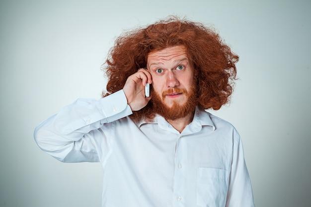 Porträt des verwirrten mannes, der am telefon eine graue wand spricht