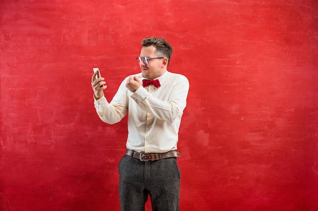 Porträt des verwirrten mannes in den gläsern, die per telefon auf einem roten studiohintergrund sprechen