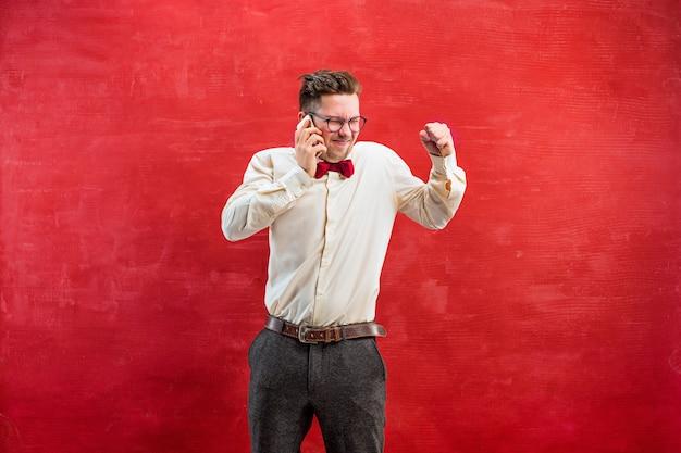 Porträt des verwirrten mannes in der brille, die per telefon auf einem roten studio spricht