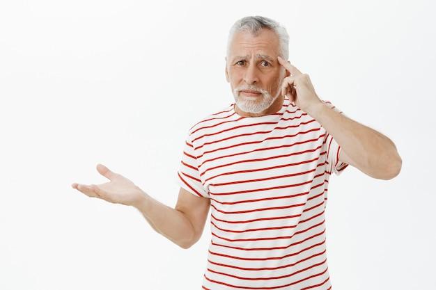 Porträt des verwirrten und verärgerten bärtigen älteren mannes, der person schimpft, die dumm handelt