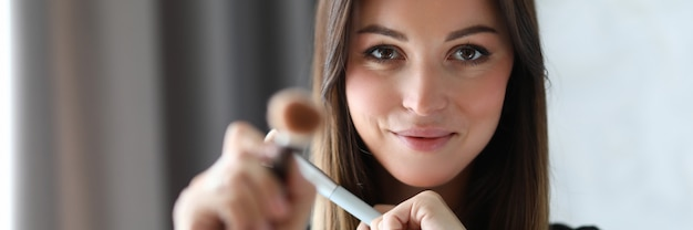 Porträt des visagisten, der kamera mit schüchternheit und freude betrachtet. lächelnder visagist mit speziellen und professionellen werkzeugen. beauty- und maquillage-konzept