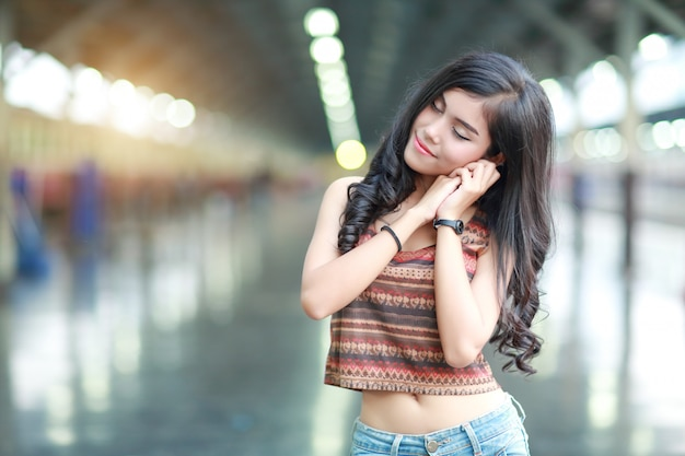 Porträt des wartezugs der jungen reisendfrau und des bekanntgebenden symbols der guten nacht