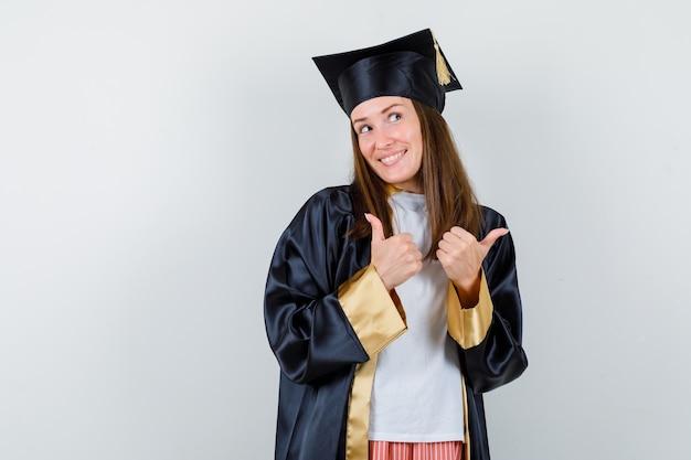 Porträt des weiblichen absolventen, der doppelte daumen in uniform, freizeitkleidung zeigt und glückliche vorderansicht schaut