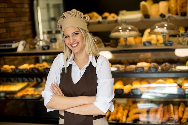 Porträt des weiblichen bäckers mit frischem brot lächelnd in der bäckerei
