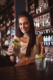 Porträt des weiblichen bartenders, der ein glas cocktail hält