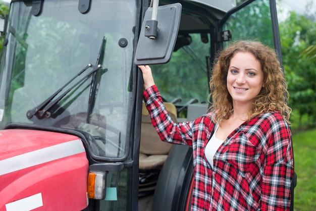 Porträt des weiblichen bauern, der durch die traktormaschine im obstgarten steht