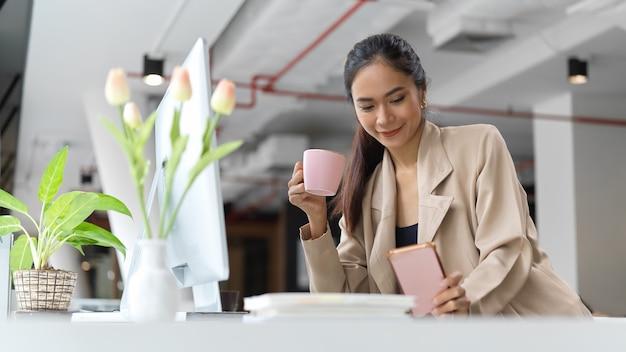 Porträt des weiblichen büroangestellten, der mit smartphone und einer tasse kaffee beim arbeiten im büroraum entspannt