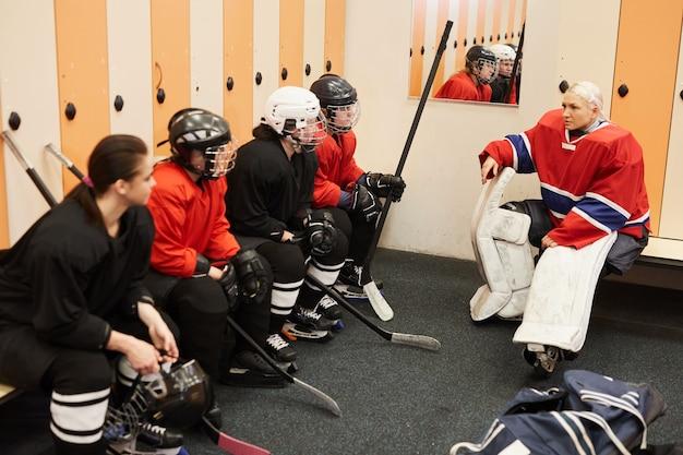 Porträt des weiblichen eishockeymannschaftskapitäns, der motivierenden aufmunterungsgespräch im umkleideraum gibt