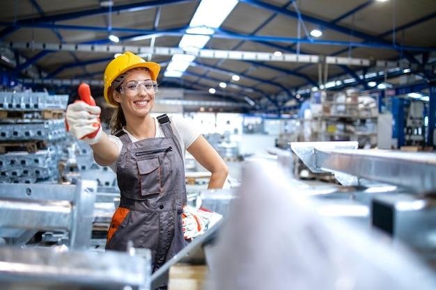 Porträt des weiblichen fabrikarbeiters, der daumen hoch hält
