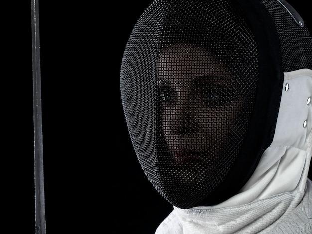 Porträt des weiblichen fechters, der rapier hält. konzept für olympische sportarten, kampfsport, angriff und professionelles training