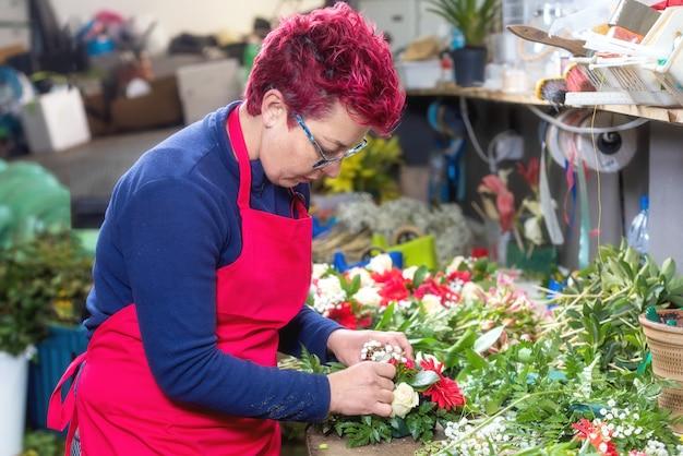 Porträt des weiblichen floristen schönen blumenstrauß am blumenladen herstellend.
