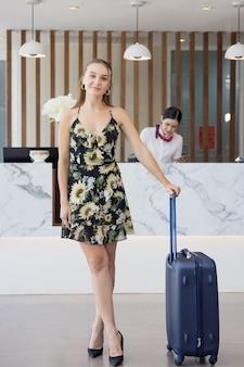 Porträt des weiblichen gastes mit gepäck, das darauf wartet, im hotel einzuchecken, glückliches reiselebensstilkonzept