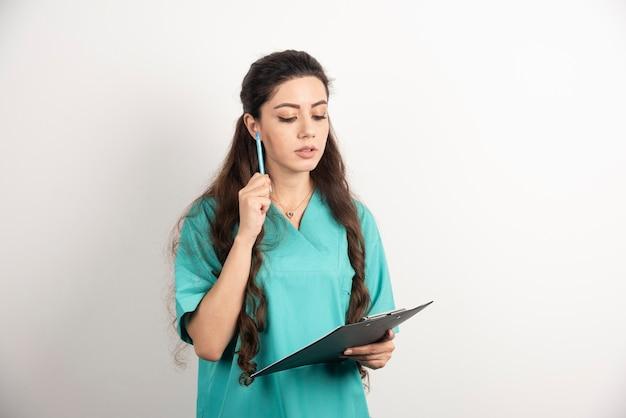 Porträt des weiblichen gesundheitspersonals auf weißer wand.