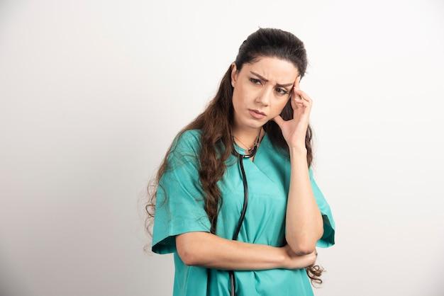 Porträt des weiblichen gesundheitspersonals, das ihren kopf berührt.