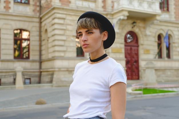 Porträt des weiblichen hippies mit natürlichem make-up und kurzem haarschnitt freizeit draußen genießend