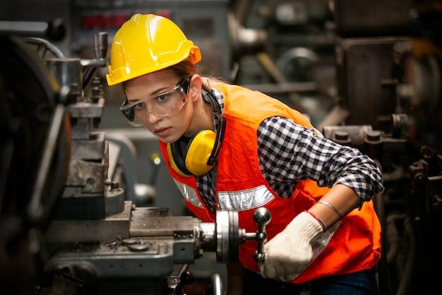 Porträt des weiblichen ingenieurs, der an cnc-maschine arbeitet, die gegen fabrikumgebung steht.