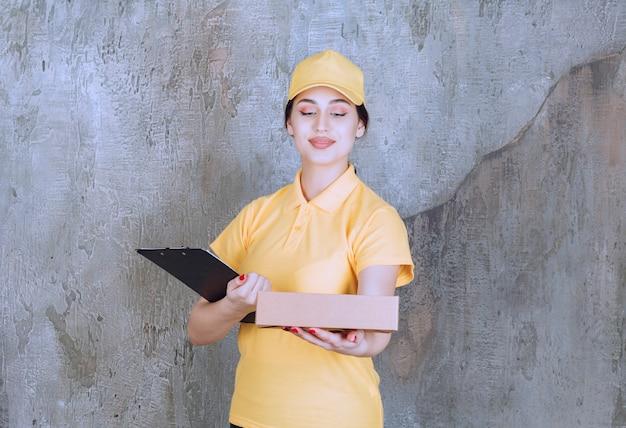 Porträt des weiblichen kuriers, der klemmbrett mit karton hält