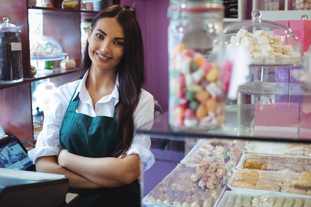 Porträt des weiblichen ladenbesitzers, der am türkischen süßigkeitenzähler steht