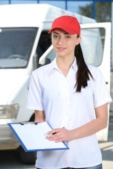 Porträt des weiblichen lieferungsfahrers mit klemmbrett und kasten.