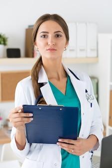 Porträt des weiblichen medizintherapeutenarztes im weißen kittel, der klemmbrett im büro hält