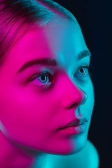 Porträt des weiblichen modemodells im neonlicht auf dunklem studio