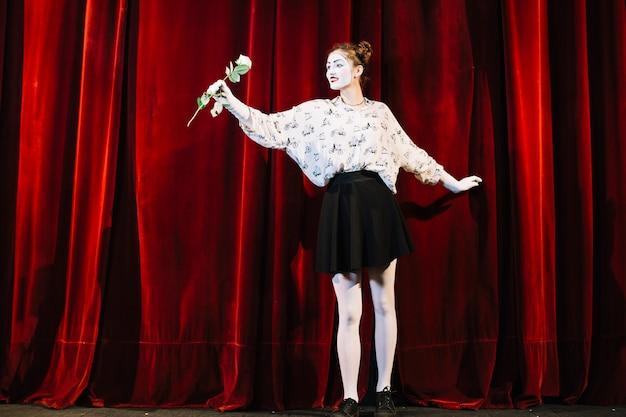 Porträt des weiblichen pantomimen stehend vor dem roten vorhang, der weißrose hält