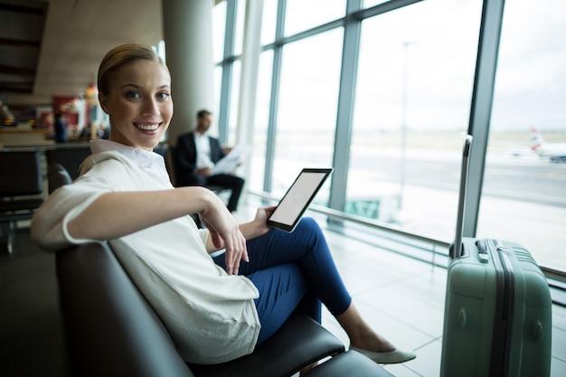 Porträt des weiblichen pendlers mit digitalem tablett, das im wartebereich sitzt