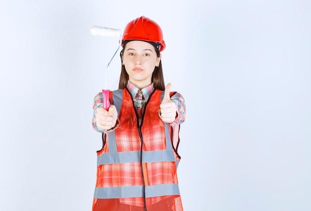 Porträt des weiblichen reparateurs in der uniform, die anstrichrolle über weißer wand hält.