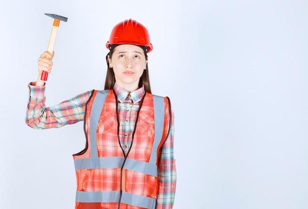 Porträt des weiblichen reparateurs in der uniform, die hammer über weißer wand hält.