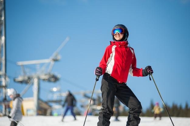 Porträt des weiblichen skifahrers stehend mit skis auf die gebirgsoberseite an einem winterurlaubsort am sonnigen tag