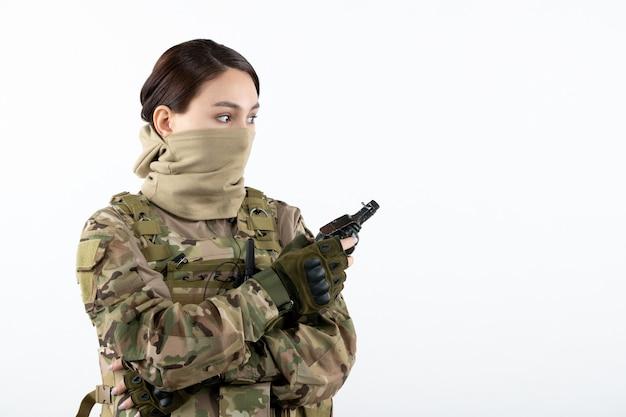 Porträt des weiblichen soldaten mit granate in der weißen wand der tarnung