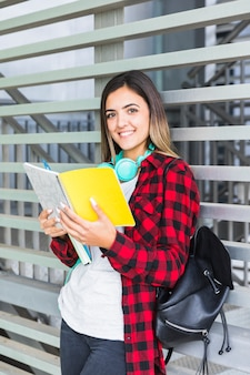 Porträt des weiblichen studenten, der in der hand das buch lächelt an der kamera hält