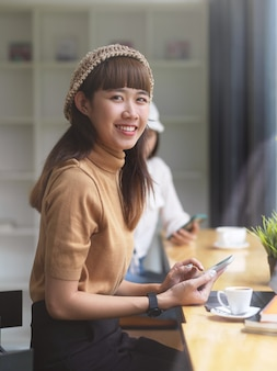 Porträt des weiblichen teenagers, der in kamera schaut, während aufgabe im café tut