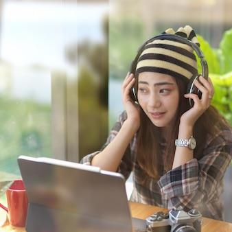 Porträt des weiblichen teenagers, der musik mit kopfhörer beim entspannen im café hört