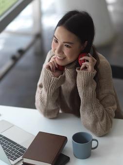 Porträt des weiblichen teenagers im pullover mit kopfhörer, der im co-arbeitsraum entspannt
