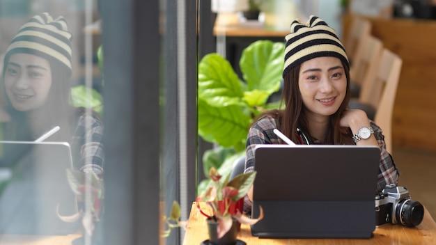 Porträt des weiblichen teenagers unter verwendung der digitalen tablette auf ihrem schoß, während im gemeinsamen arbeitsraum sitzend