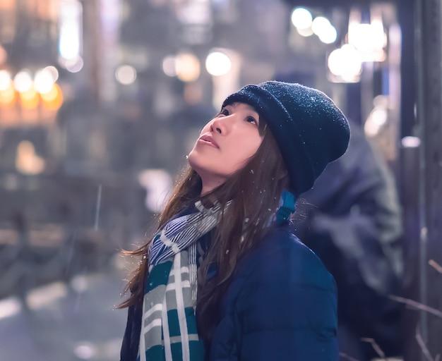 Porträt des weiblichen touristen, der in ginzan onsen mit nachts fallendem schnee reist