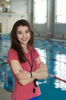Porträt des weiblichen trainers, der mit verschränkten armen in der nähe des pools steht.