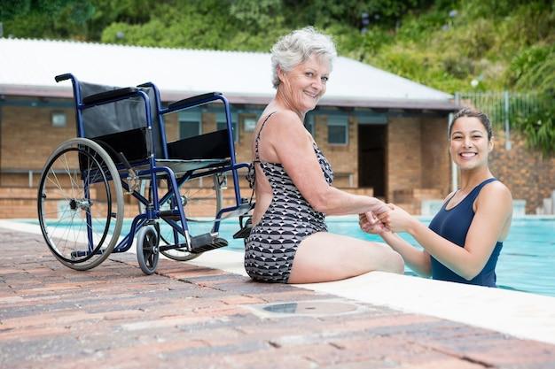 Porträt des weiblichen trainers und der älteren frau, die am pool lächeln
