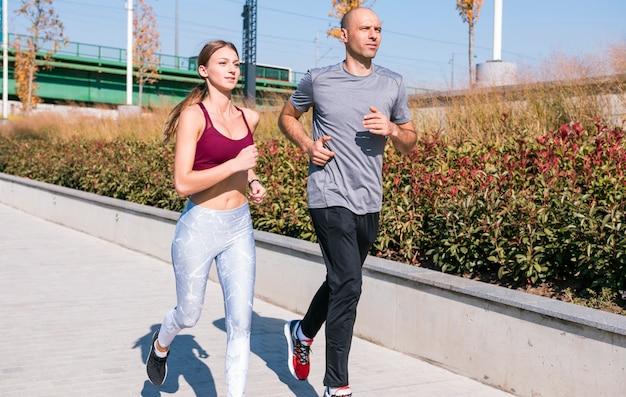 Porträt des weiblichen und männlichen athleten, der zusammen in park läuft