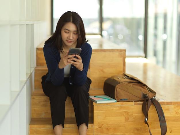 Porträt des weiblichen universitätsstudenten unter verwendung des smartphones beim entspannten sitzen im gemeinsamen arbeitsraum