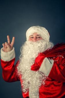 Porträt des weihnachtsmannes, der eine tasche mit geschenken trägt