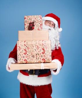 Porträt des weihnachtsmannes, der stapel von weihnachtsgeschenken hält
