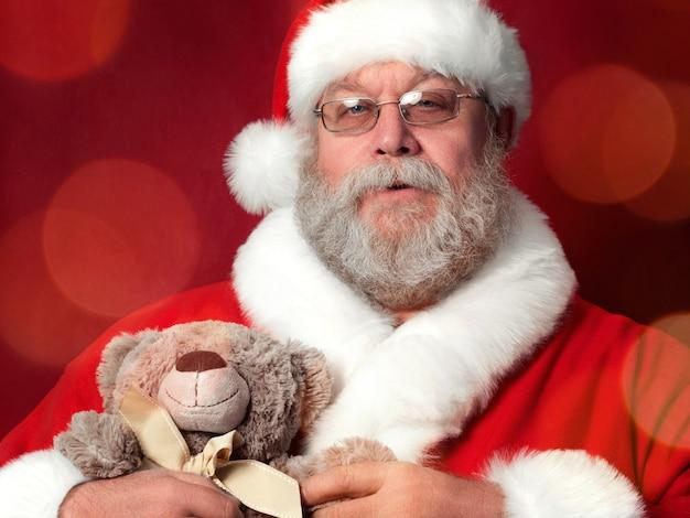 Porträt des weihnachtsmannes, der teddybär hält.