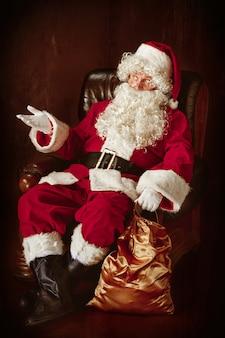 Porträt des weihnachtsmannes im roten kostüm, das im sessel sitzt