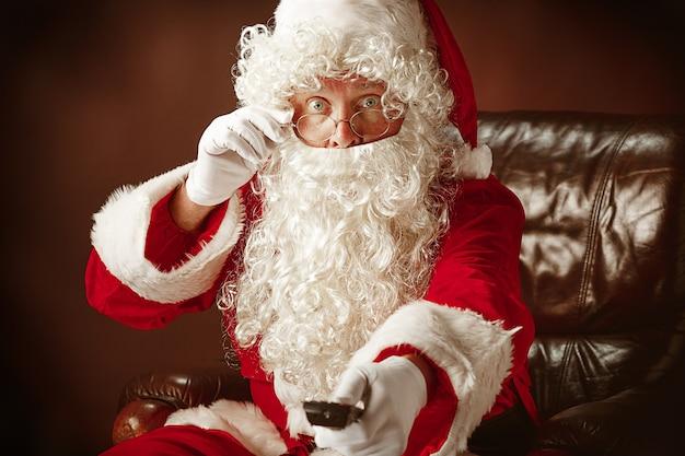 Porträt des weihnachtsmannes im roten kostüm mit tv-fernbedienung