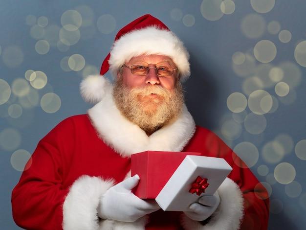 Porträt des weihnachtsmannes mit geöffneter geschenkbox.
