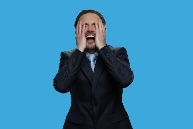 Porträt des weinenden geschäftsmannes lokalisiert auf blauem hintergrund. mann im anzug, der sein gesicht mit beiden händen berührt. ausfall- oder problemkonzept.