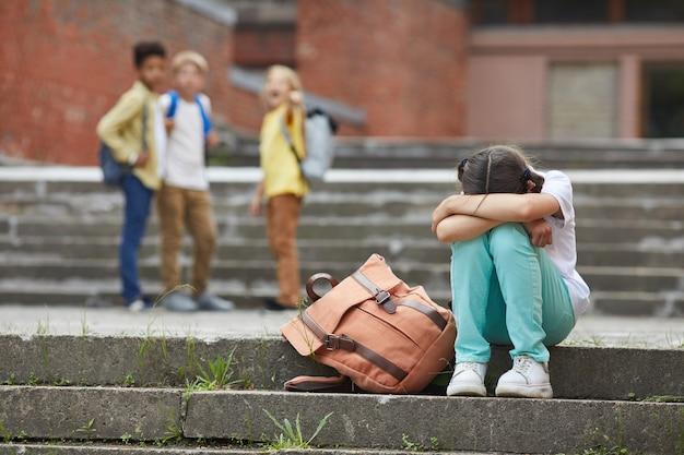 Porträt des weinenden schulmädchens in voller länge, das draußen auf treppen mit einer gruppe von neckenden kindern sitzt, die sie im hintergrund schikanieren, kopieren raum